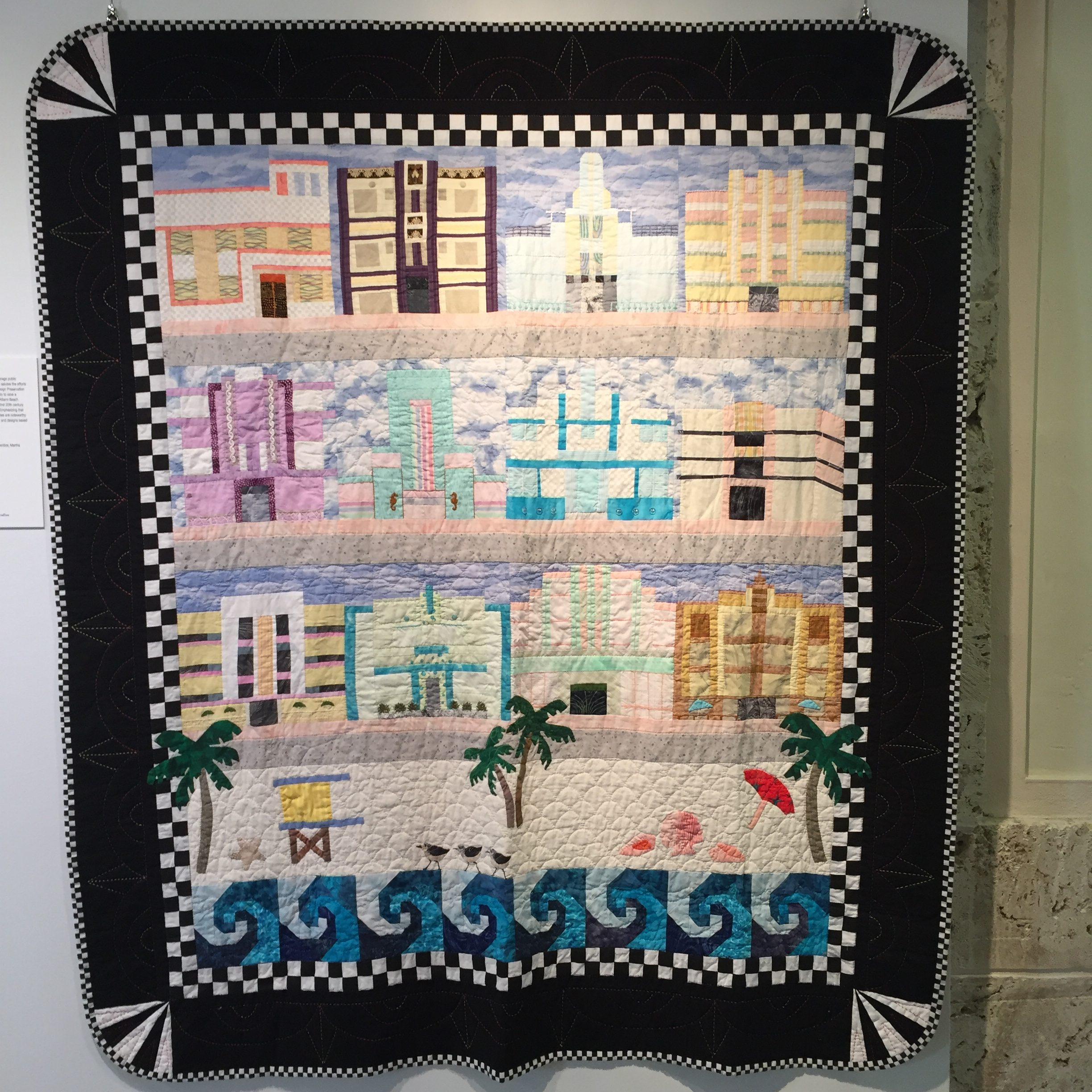 """Art Deco SoBe:  Among the successes of The Villagers is their ability to encourage public awareness of the Country's distinctive architecture.  This quilt salutes the efforts of activists like Barbara Baer Capitman, founder of Miami Design Preservation League (1977) who, along with many others, worked tirelessly to save a number of Art Deco (ca. 1929-1940) buildings in the City of Miami Beach.  These South Beach (SoBe) buildings represent the nation's first 20th century Historic District to be listed in the National Register (1979).  Emphasizing that they are located in a seaside resort, SoBe's Tropical Deco sites are noteworthy for their pastel colors, floral and aquatic applied decoration, and designs based on ocean liners.       Artists: Louise Petrine, Joyce Seibert, Toni Garcia, Cathy Prentice, Martha Stockhausen, Joan Bounds, Jo Walters  2001-2002, 50"""" wide x 60"""" long"""