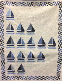 """Biscayne Bay Regatta: The blue-and-white quilt depicts sailboats racing on beautiful Biscayne Bay. Villagers all worked on this lovely project.  Artists:  Louise Bennett, Joan Bounds, Jeanne Bunten, Louise Petrine, Jan Sauvigne  2019-2020, ?"""" wide x ?"""" long"""